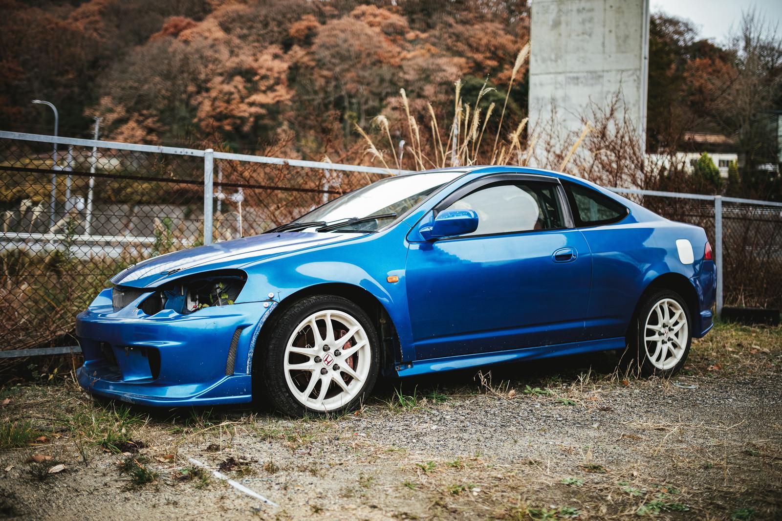 「ヘッドライトが外された青い自動車」の写真