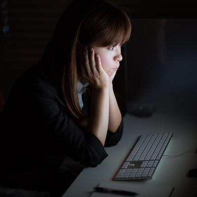 「暗いオフィスで孤独に残業するOL」の写真素材