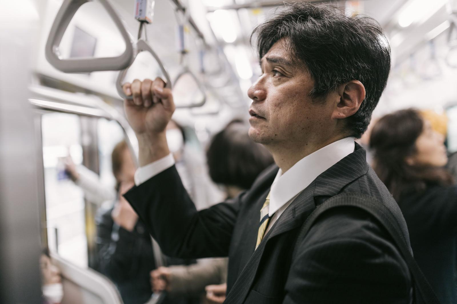 「単身赴任で満員電車に揺られて通勤するお父さん」の写真[モデル:よたか]