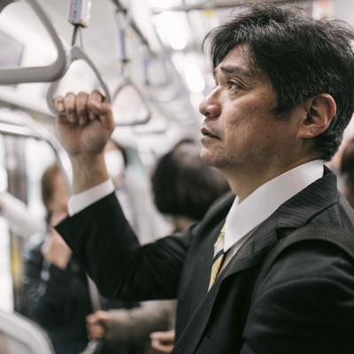「単身赴任で満員電車に揺られて通勤するお父さん」の写真素材