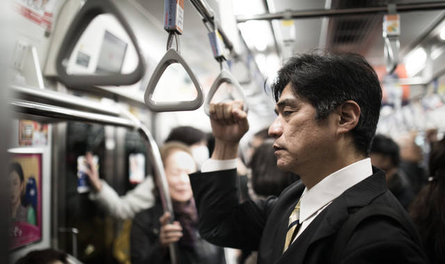夜遅くまで勤めて終電で帰る会社役員の写真