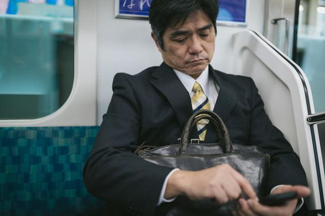 通勤中にニュースアプリを確認するサラリーマンの写真
