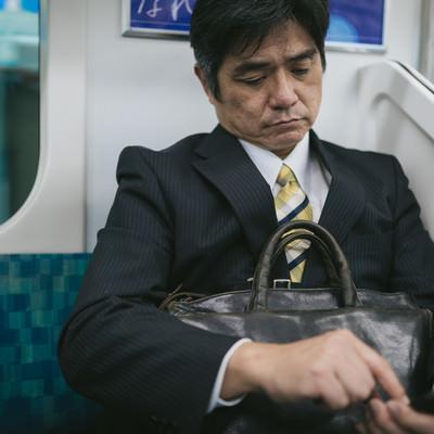「通勤中にニュースアプリを確認するサラリーマン」の写真素材