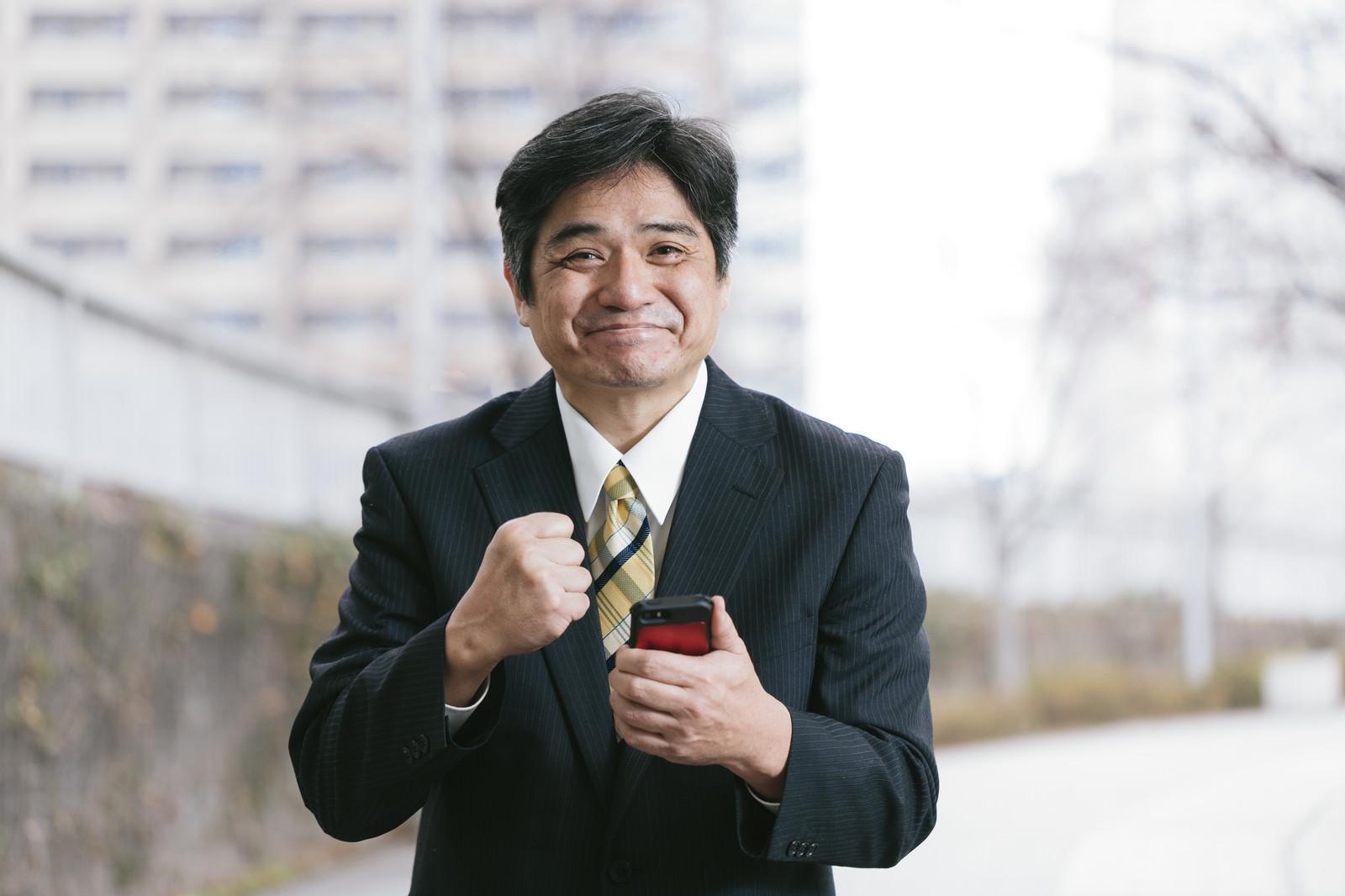 「今月の売り上げ目標を達成して喜ぶ管理職」の写真