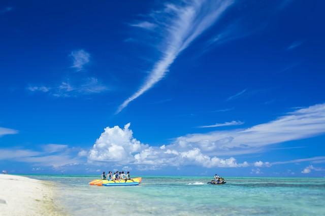 沖縄の海とバナナボートの観光客の写真