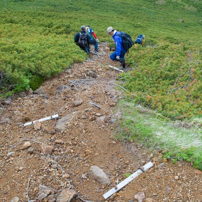 足場の悪い登山道の傾斜を下る登山者の写真