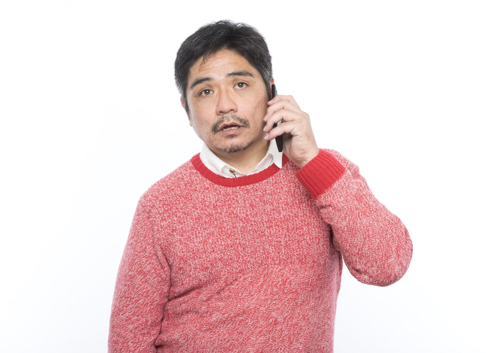 「呆れた様子で電話をするお父さん」の写真[モデル:よたか]
