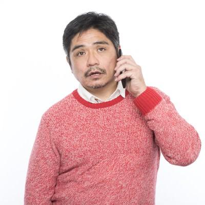「呆れた様子で電話をするお父さん」の写真素材