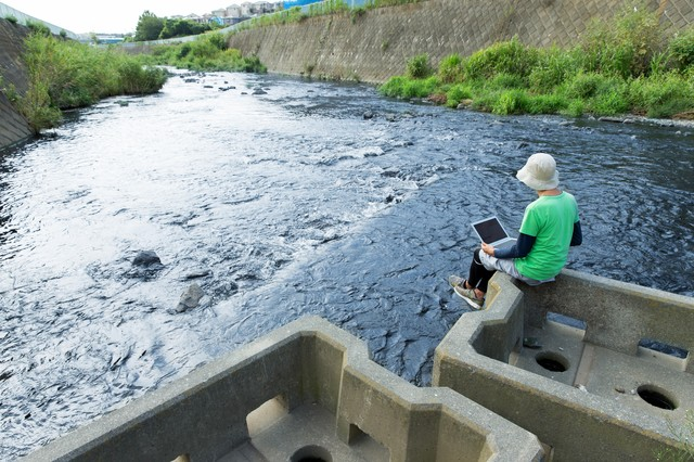 川の流れにデータの流れを重ねて想いを馳せるマーケターの写真