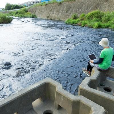 「川の流れにデータの流れを重ねて想いを馳せるマーケター」の写真素材