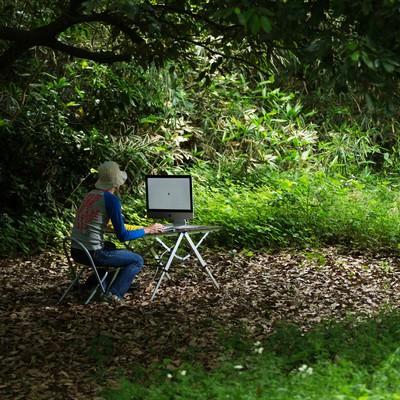 「アップデートがなかなか終わらず森の中でおいてけぼりの新卒デザイナー」の写真素材