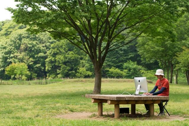 僕の職場は緑に包まれた公園のテーブルの写真
