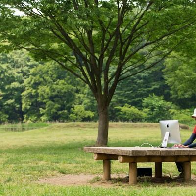 「僕の職場は緑に包まれた公園のテーブル」の写真素材