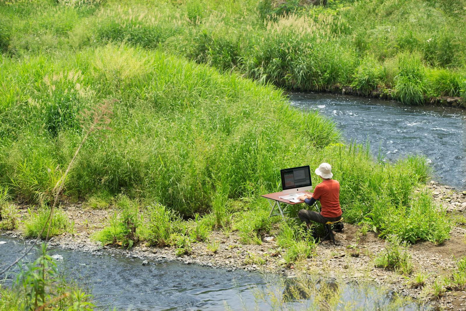 「川のせせらぎを求めて下流の中洲で作業をするノマドワーカー」の写真
