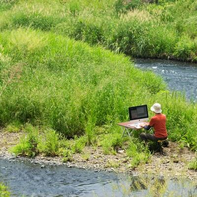 「川のせせらぎを求めて下流の中洲で作業をするノマドワーカー」の写真素材