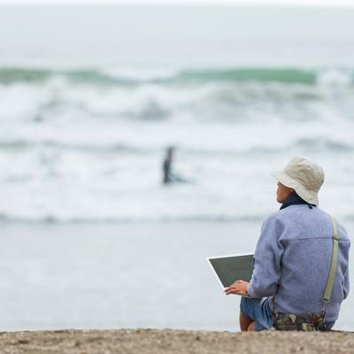 「サーファーの同僚に海へ連れて行かれるも、まわりの雰囲気に溶け込めずコーディングをはじめてしまうデザイナー」の写真素材