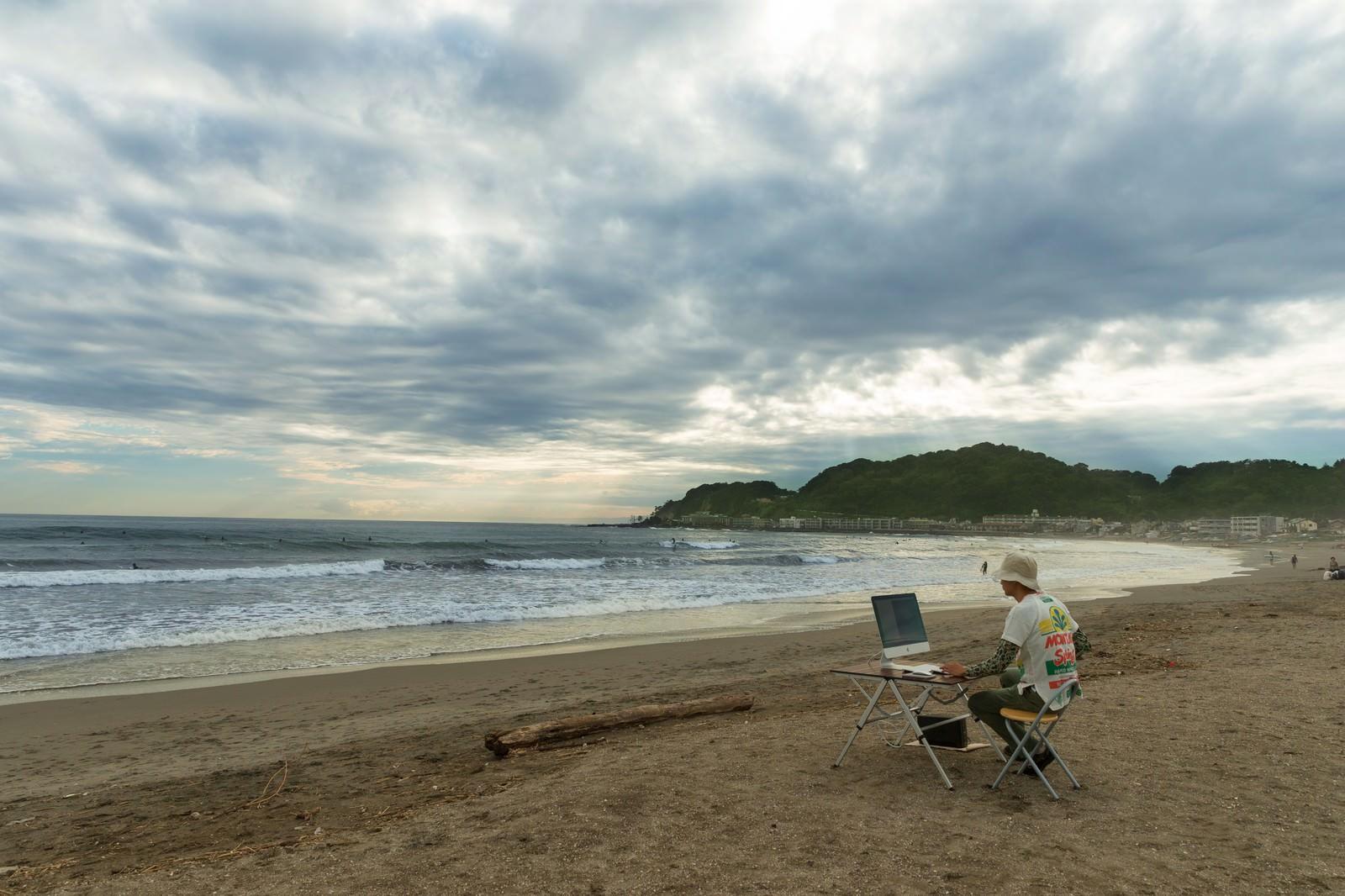 「徹夜しすぎて浜辺でコーディングしているかの幻覚をみているWebデザイナー」の写真