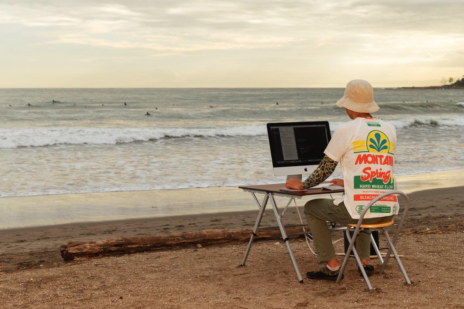 「本当に浜辺でコーディングしているWebデザイナー」の写真
