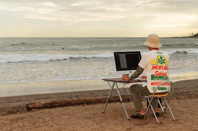 本当に浜辺でコーディングしているWebデザイナーの写真