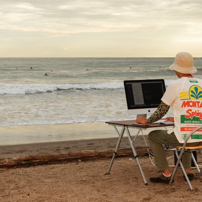 「本当に浜辺でコーディングしているWebデザイナー」の写真素材