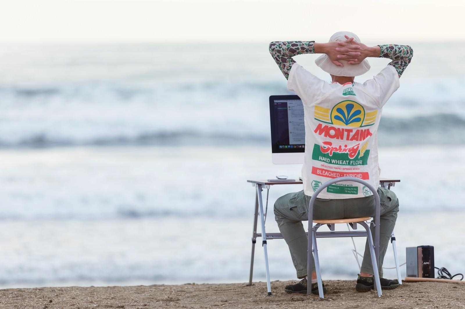 「浜辺がオフィスと化したWebデザイナー | ぱくたそフリー素材」の写真