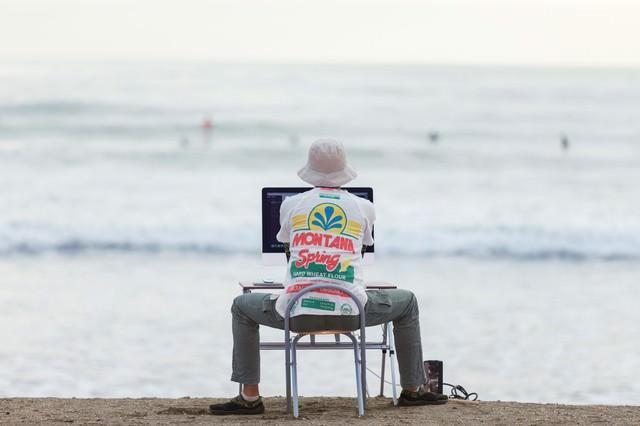 サーファーを眺めながら、サーファーのWebサイトを仕上げる意識の高いデザイナーの写真