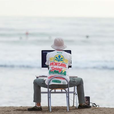 「サーファーを眺めながら、サーファーのWebサイトを仕上げる意識の高いデザイナー」の写真素材