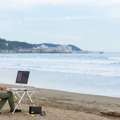 「上司に「今どこ?」と聞かれて「浜辺です」と正直に応えるWebデザイナー」の写真素材