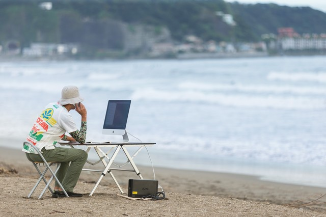 上司に「早く帰ってこい!」「すぐには帰れませんよ浜辺ですから」と正直に答えるWebデザイナーの写真