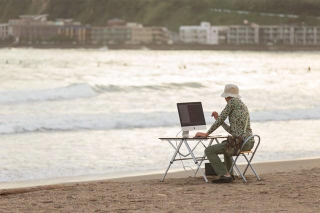 サーフィンをしに海へ来たのに、ついついコーディングしてしまうIT戦士の写真