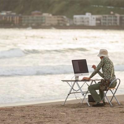 「サーフィンをしに海へ来たのに、ついついコーディングしてしまうIT戦士」の写真素材