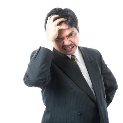「手形不渡りが発生して頭を抱える経営者」の写真素材