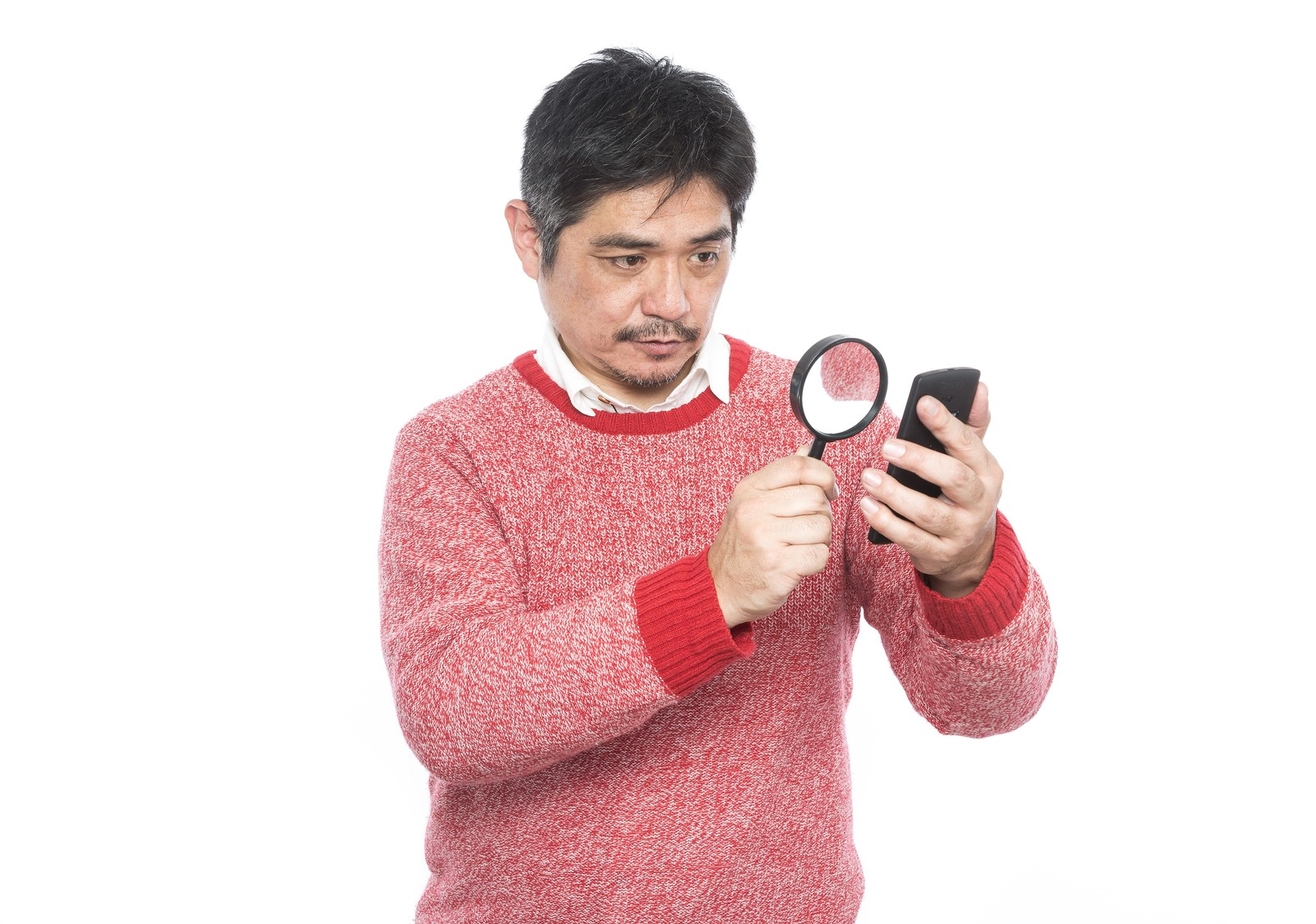 「フォントサイズが小さい為、拡大鏡を使って閲覧する中年男性」の写真[モデル:よたか]