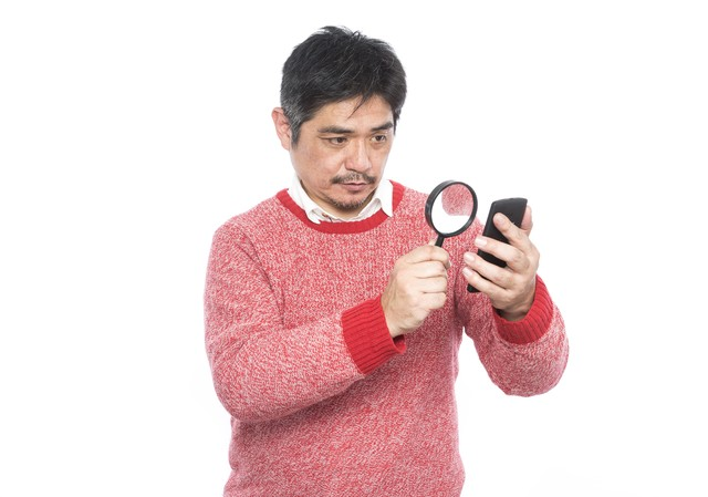 フォントサイズが小さい為、拡大鏡を使って閲覧する中年男性の写真