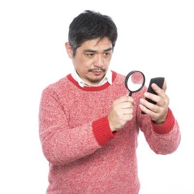 「フォントサイズが小さい為、拡大鏡を使って閲覧する中年男性」の写真素材