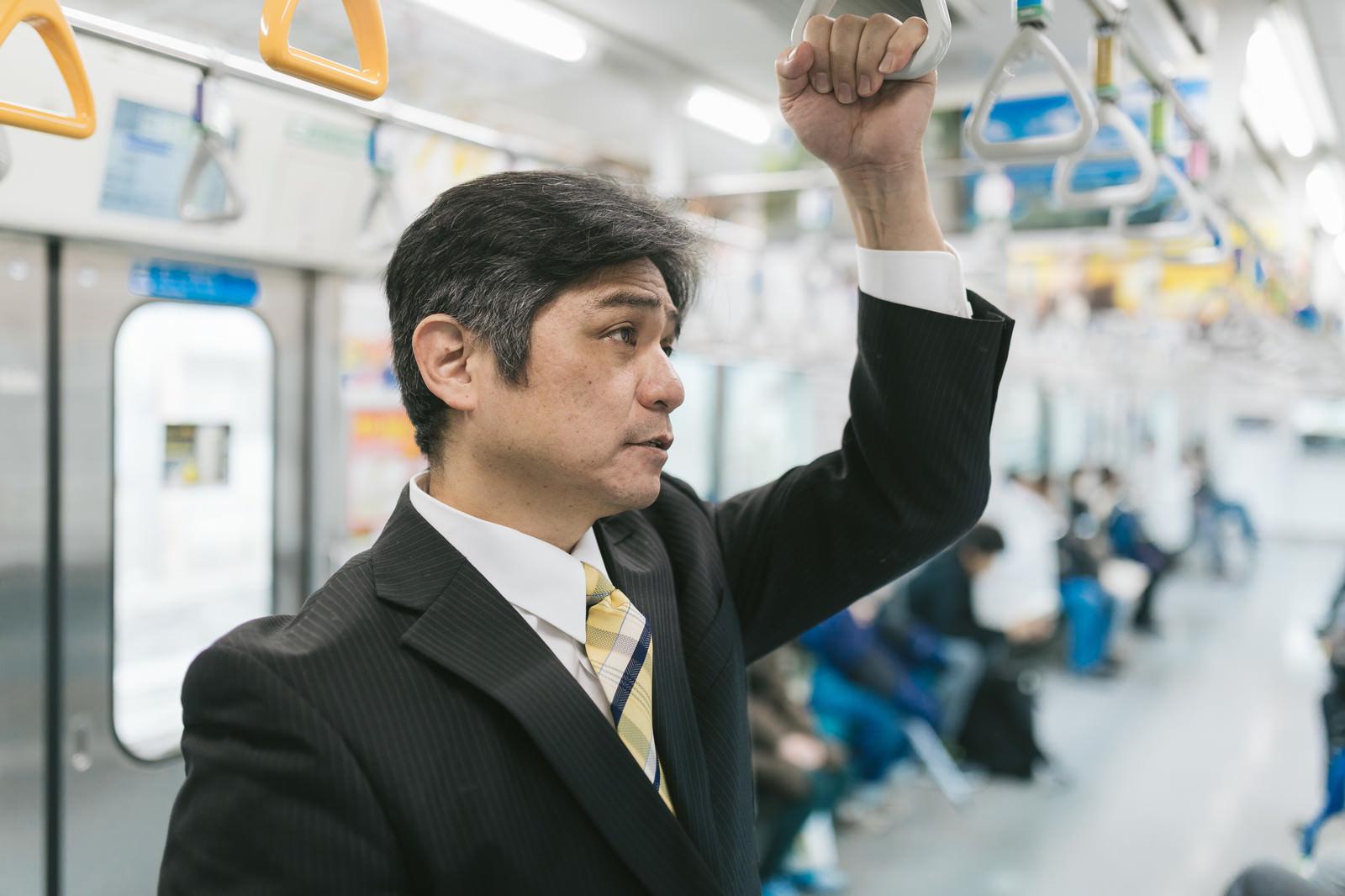 「クライアント先まで電車移動する勤続30年選手」の写真[モデル:よたか]