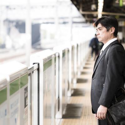 「駅のホームで険しい表情の中年会社員」の写真素材