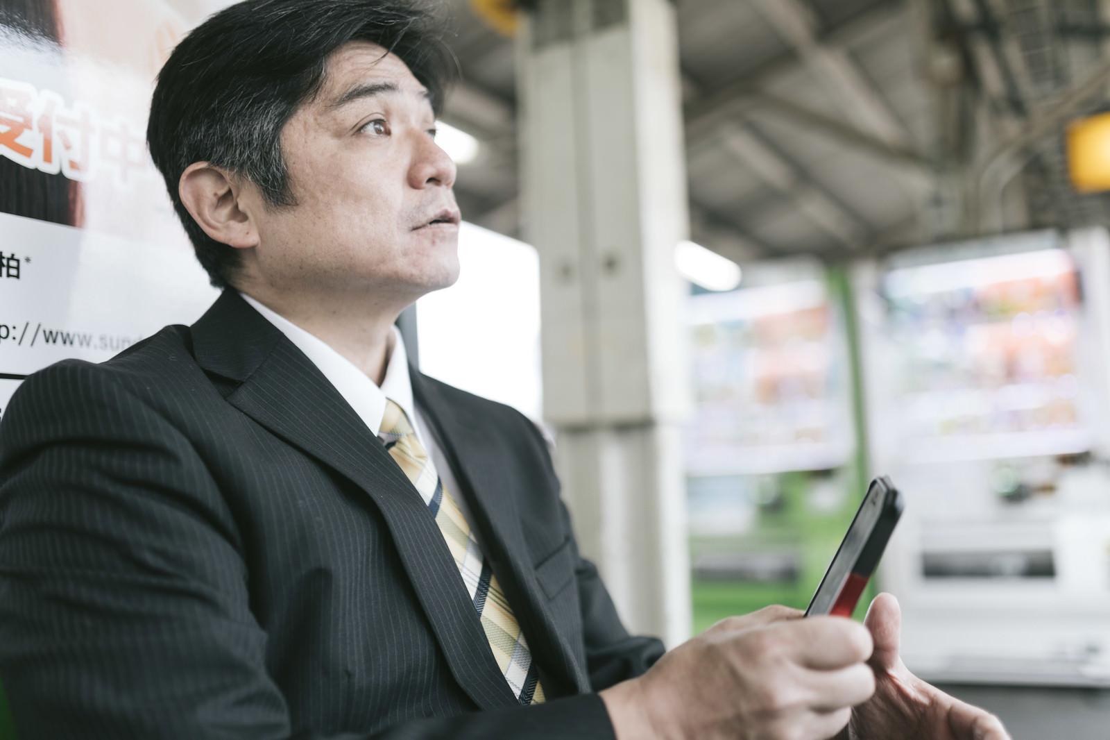 「駅のベンチでスマホに熱中してて電車がいってしまった上司」の写真[モデル:よたか]