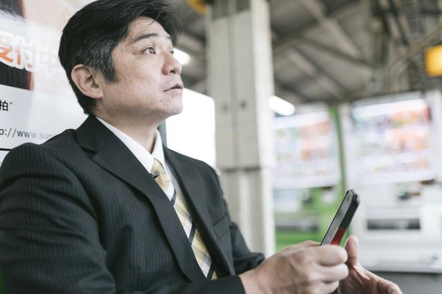 駅のベンチでスマホに熱中してて電車がいってしまった上司の写真