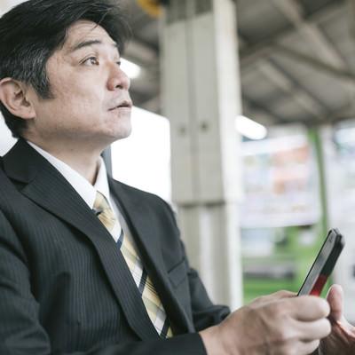 「駅のベンチでスマホに熱中してて電車がいってしまった上司」の写真素材