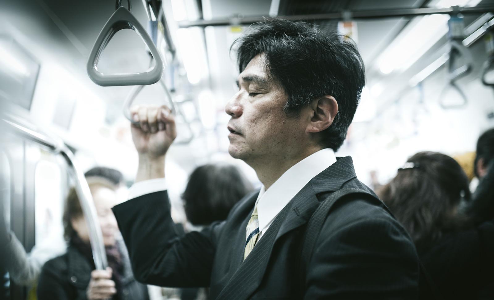 「電車の中で、立ったまま寝る中年男性」の写真