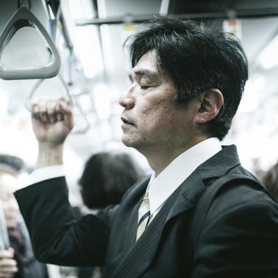 「電車の中で、立ったまま寝る中年男性」の写真素材