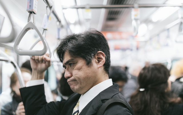 電車内の迷惑行為を見て思わずイラッとくる中年の男性の写真
