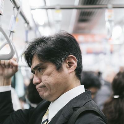 「電車内の迷惑行為を見て思わずイラッとくる中年の男性」の写真素材