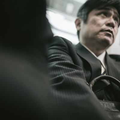 「満員電車で「降ります」がなかなか言えない弱腰中年」の写真素材