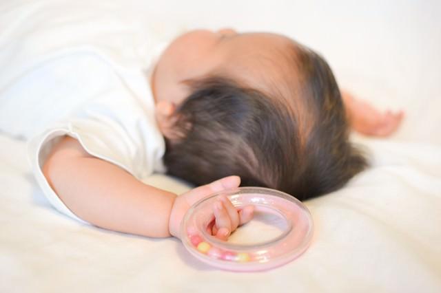 寝ながら両手をあげる新生児の写真