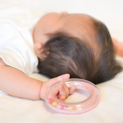 「寝ながら両手をあげる新生児」の写真素材