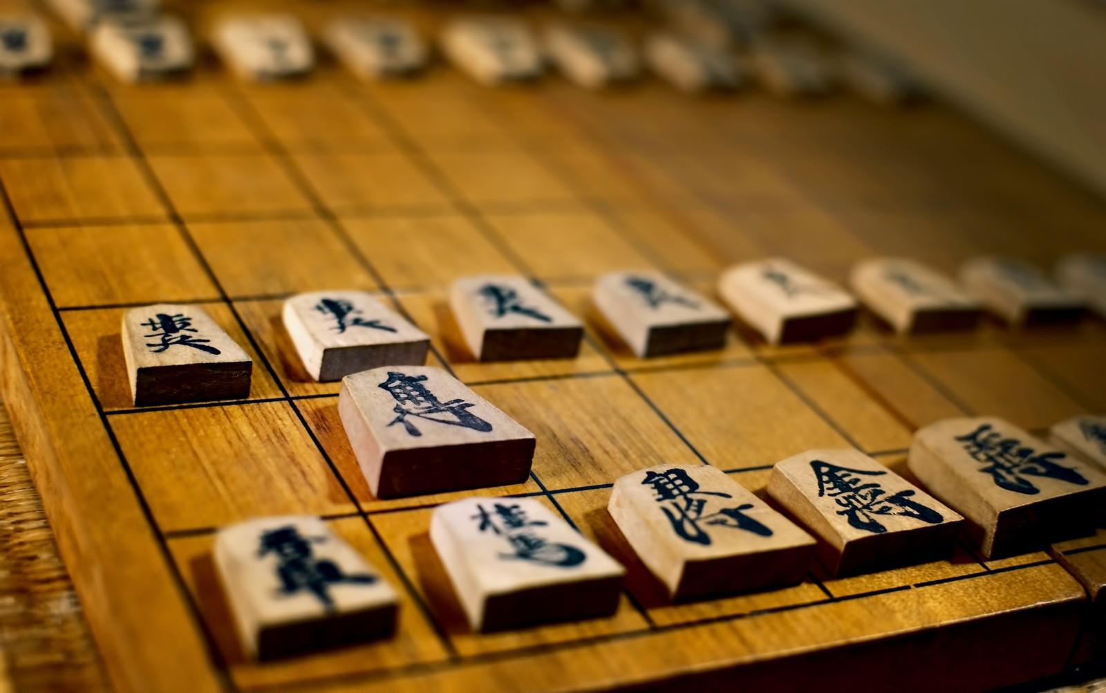 「古く使い込まれた将棋盤と駒」の写真