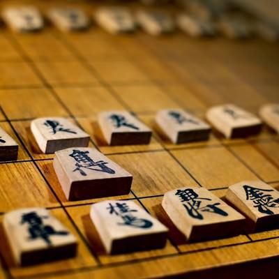 古く使い込まれた将棋盤と駒の写真