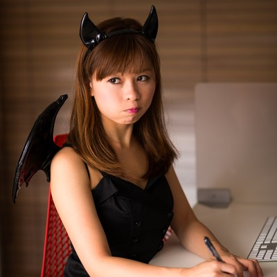「ハロウィンで小悪魔のコスプレを強要された事務の女性」の写真素材